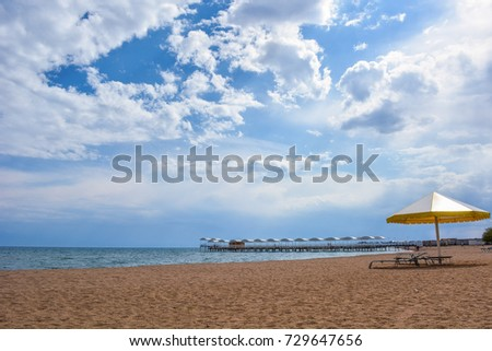 Beautiful scenic view - distant open wood amid the calm water of Issyk-Kul Lake against the background of Tien Shan mountain range and cloudy blue sky, Kyrgyzstan, Central Asia #729647656