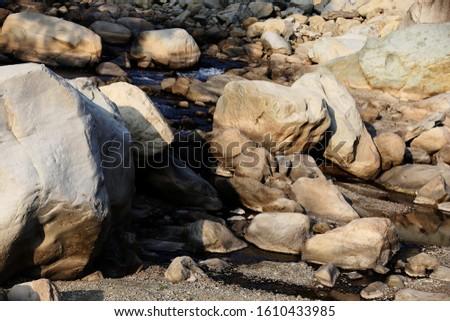 Beautiful scenic view of flowing water between stones in Uttarakhand, India.