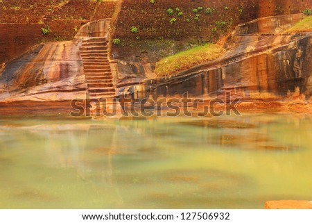 Beautiful scenic view of green pond water against the background of carved wall with scale in Sigiriya Ancient Fortress (Lion's Rock) - UNESCO World Heritage Site, Sri Lanka island, South Asia