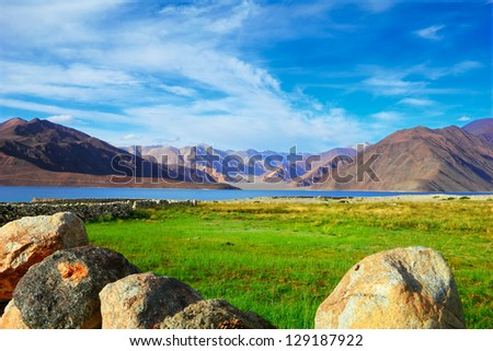 Beautiful scenic view of Pangong lake against the background of distant colorful mountain range and cloudy blue sky with green field and well rounded stones, Ladakh, Jammu & Kashmir, Northern India #129187922