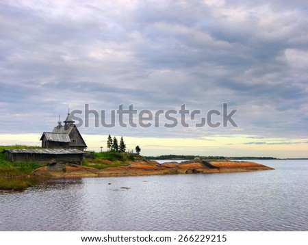Beautiful scenic view of wooden Russian Orthodox church on the shore of White Sea against the background of dramatic cloudy sky in Rabocheostrovsk, Republic of Karelia, Northern Russia #266229215