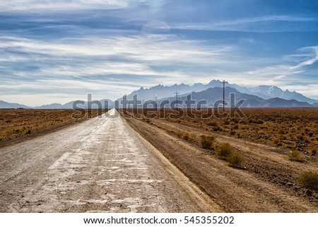 Beautiful scenic view - twisty road across the dry arid land between barren mountains against the background of vivid blue sky. Road to Abyaneh, Iran #545355202