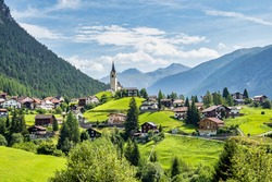 Beautiful Schmitten village at Albula pass in Grisons, Graubuenden, Switzerland with view of houses on green grassy hills, a lovely church on hilltop and majestic mountains in background