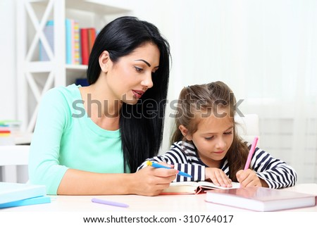 Beautiful school girl doing homework with mother at home