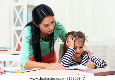Beautiful school girl doing homework with mother at home #312900947