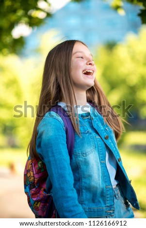 Beautiful schoolgirl girl. Summer in nature. Dressed in jeans clothes behind her backpack. Concept back to school. Emotion of happiness pleasure pleasure, bright children's laughter. #1126166912