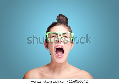beautiful screaming girl with green eyeglasses on gray background