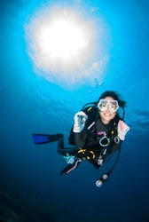 Beautiful Scuba diver woman smile cheerfully Under the blue sea With ambient light, Scubadiving Underwater concept.