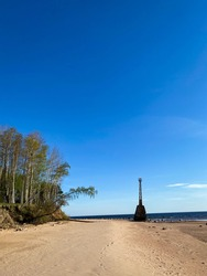 Beautiful sea beach with dune sand and an old abandoned lighthouse. The lighthouse is based on large stones. A large birch tree bends from the sandstone rock cliff across the beach.