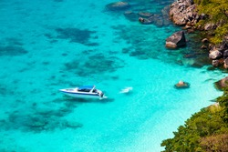 Beautiful sea landscape with tropical coast and the high-speed boat, standing near the shore