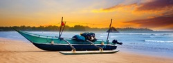 Beautiful seascape. Against the background of the sunset sky and the ocean, an old fishing boat. Sri Lanka. Wide photo.