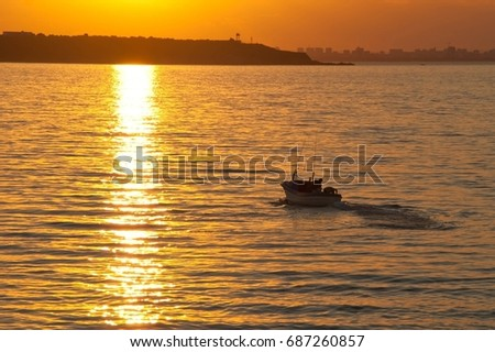 Beautiful seascape at sunset. Orange sky, small silhouette of fishing boat, floating in the sea water. Sea summer concept. #687260857