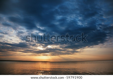 Beautiful seascape during sunset with cloudy dramatis sky - stock photo