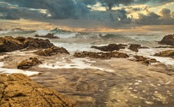 Beautiful seascape, ocean views, rocky coast, sunlight, on the horizon. Composition of nature. Sunset scenery background. Cloudy sky. Water Reflection. California Seashore.