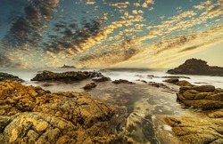 Beautiful seascape, ocean views, rocky coastline, sunlight, on the horizon. Composition of nature. Sunset scenery background. Cloudy sky. Reflection of water. California coast