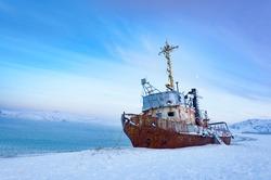 Beautiful seascape of Barents Sea with shipwreck of fishing boat on the shore in village Teriberka. Morning arctic winter landscape in Murmansk region of Russia