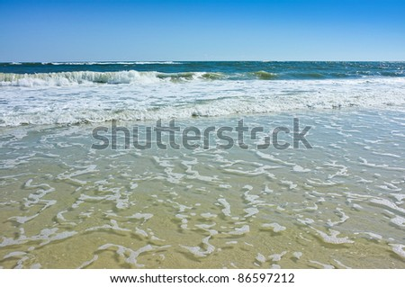 Beautiful seascape of waves, surf and foam on a warm sunny day at the beach. Good background photo.