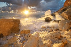 Beautiful seascape. Sea waves during storm on sunset splash on stones. Composition of nature.