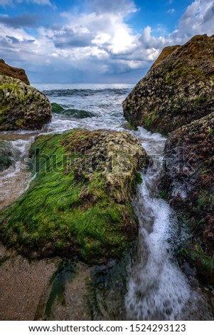 Beautiful seascape with a close view of stones with moss and flowing water between. Vertical view
