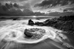 Beautiful seascape with motion waves during sunrise in black and white.