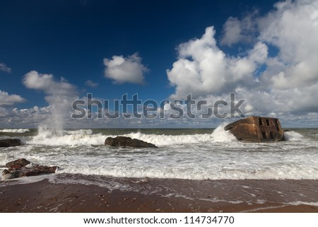 Beautiful seascape with old destroyed fort in stormy Baltic sea and blue sky with clouds