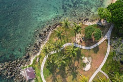 Beautiful seashore with coral, rocks, sand, light blue summer beach, coast, seawater, coral reef, coco palm. Beautiful top view of tropical and natural background. Tanjung Lesung, Banten, Indonesia.
