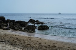 Beautiful seashore with coral, rocks, sand, light blue summer beach, coast, seawater, coral reef. Tropical and natural background. Tanjung Lesung, Banten, Indonesia.