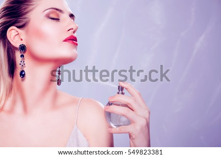 Beautiful seductive woman holding a perfume bottle and applying it