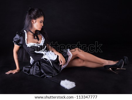 Beautiful seductive woman posing sitting on the floor in a cute little maids outfit with miniskirt