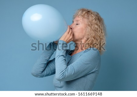 Beautiful senior blonde woman preparing for party blowing up blue balloon Foto stock ©