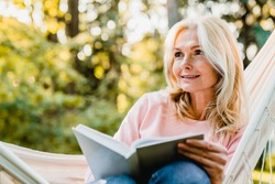 Beautiful senior blonde woman reading book and sitting in hammock in the garden