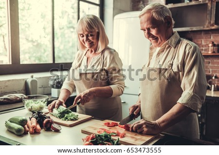 Beautiful senior couple in aprons is talking and smiling while cooking together in kitchen #653473555