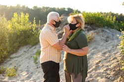 Beautiful senior couple in love wearing masks outside in beach in summer nature