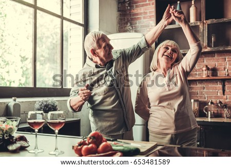 Beautiful senior couple is dancing and smiling while cooking together in kitchen