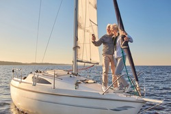 Beautiful senior couple making selfie on smartphone while standing on the side of sailboat or yacht deck floating in sea, they are hugging and smiling at camera
