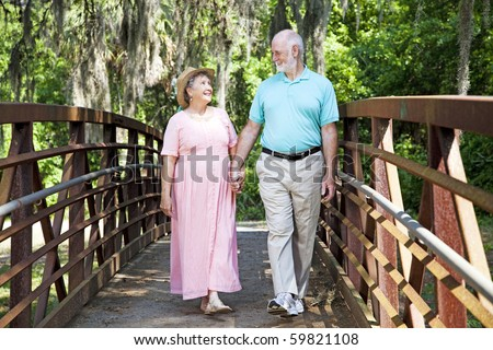 Beautiful senior couple stays fit by walking together in the park.