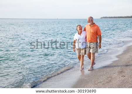 Beautiful senior couple takes a romantic stroll on a tropical beach. - stock photo