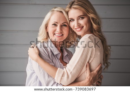 Beautiful senior mom and her adult daughter are hugging, looking at camera and smiling
