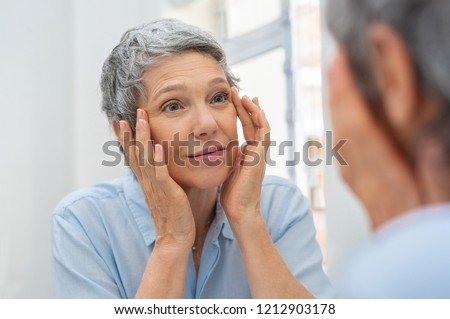 Beautiful senior woman checking her face skin and looking for blemishes. Portrait of mature woman massaging her face while checking wrinkled eyes in the mirror. Aging process concept.