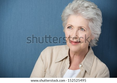 Beautiful senior woman daydreaming staring upwards with a gentle smile as she recalls nostalgic memories