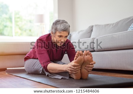 Beautiful senior woman doing stretching exercise while sitting on yoga mat at home. Mature woman exercising in sportswear by stretching forward to touch toes. Healthy active lady doing yoga.