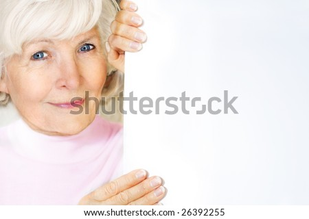 Beautiful senior woman holding blank board with space for text
