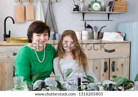 Beautiful senior woman in green pullover with her granddaughter sitting at the festive table against kitchen interior background. Portrait of cheerful sixty-year-old grandmother.