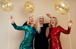 Beautiful senior woman making party and celebrating new year. Middle aged women wearing elegant glittering dresses and having fun. Studio portraits on colored background