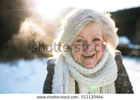 Beautiful senior woman on a walk, covered by snow #552120466