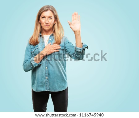 Beautiful senior woman smiling confidently while making a sincere promise or oath, solemnly swearing with one hand over heart.