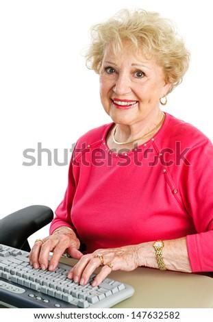 Beautiful senior woman typing on a desktop computer keyboard.  White background.   - stock photo