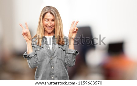 Beautiful senior woman with a proud, happy and confident expression; smiling and showing off success while gesturing victory with both hands, giving an