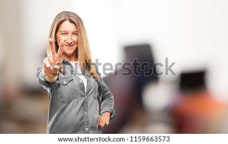 Beautiful senior woman with a proud, happy and confident expression; smiling and showing off success while gesturing victory, giving an