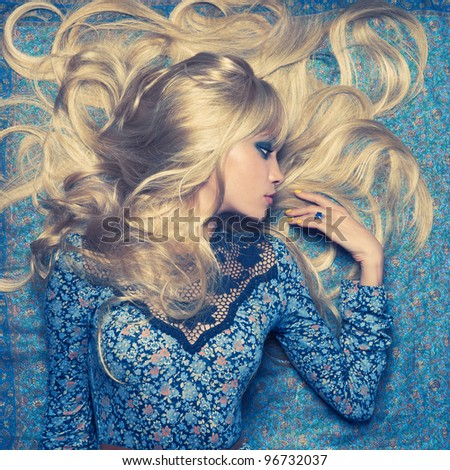 Beautiful sensual blonde lying on a blue pattern
